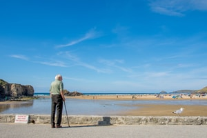 man stands and looks the low tide view of the beach