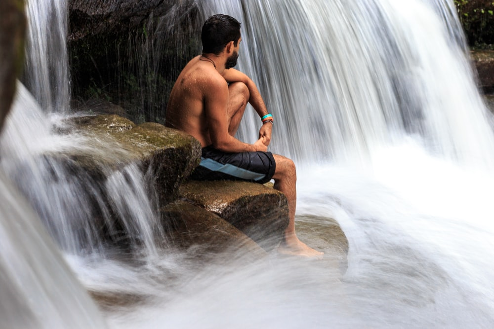 topless man sits on rock between waterfall