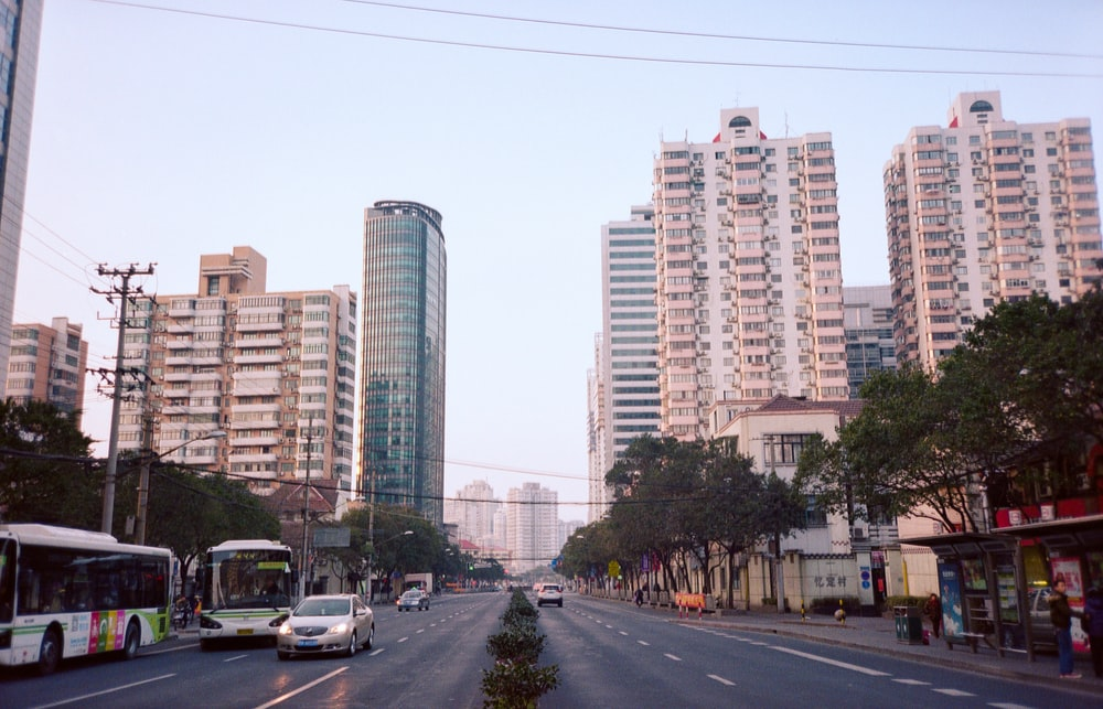 different vehicles on road viewing city with high-rise buildings during daytime