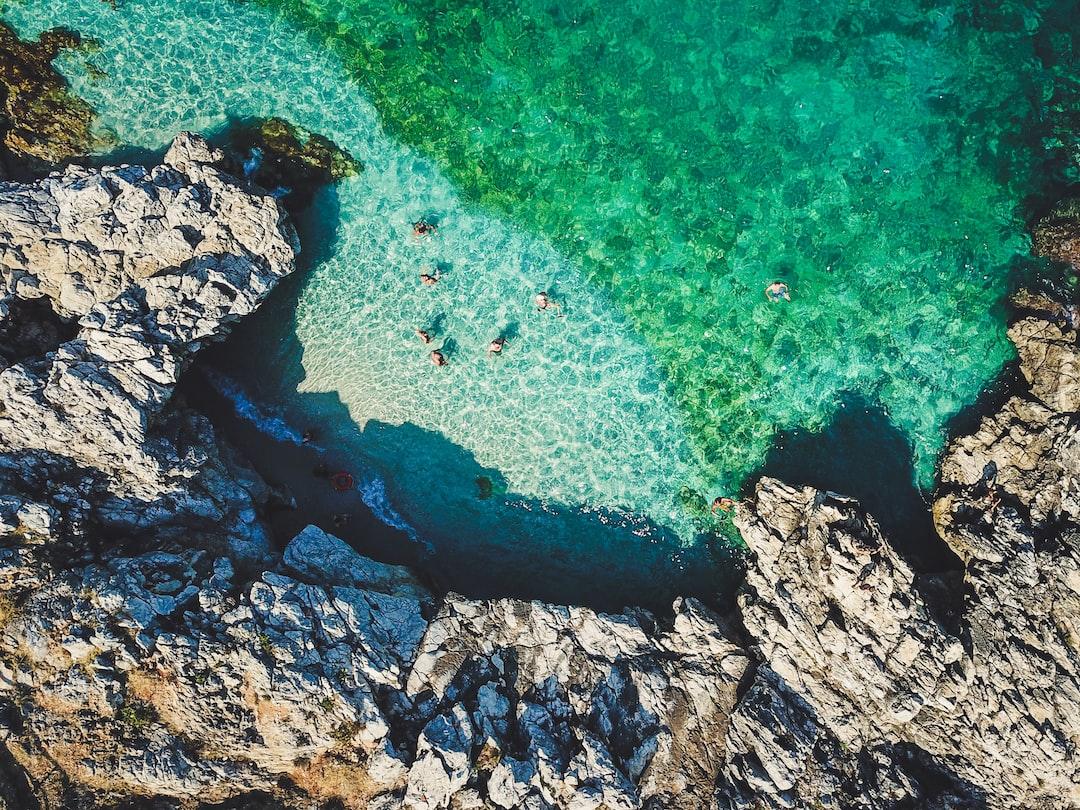 Beach, clear water, rocks, drone, people