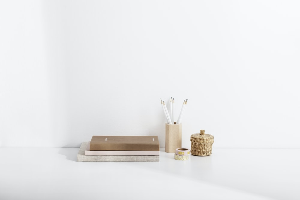 several books beside a pen holder and canister