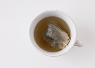 tea in white ceramic mug near yellow gerbera daisy flowers