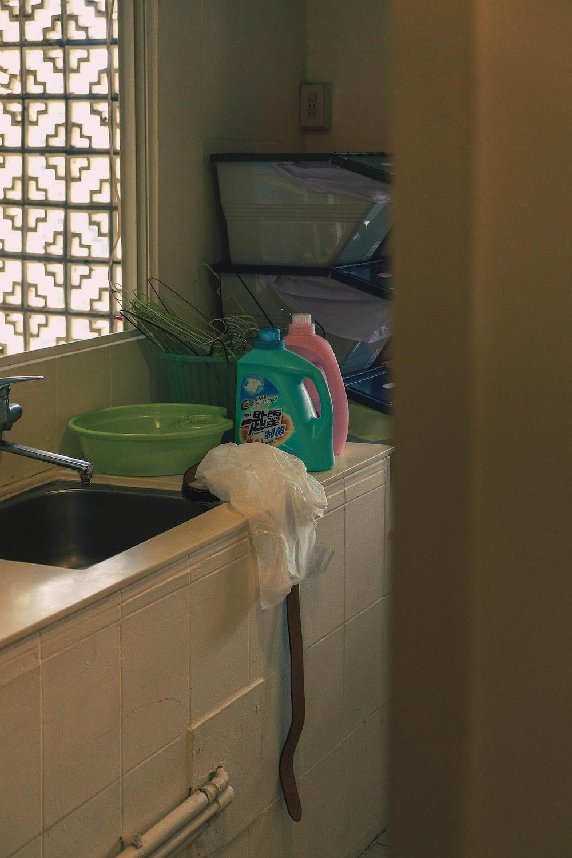 white fabric near round green plastic pail
