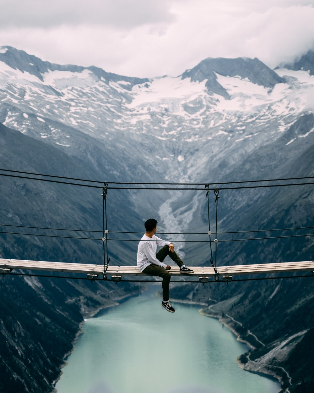 man wearing white crew-neck long-sleeved shirt sitting on beige wooden footbridge viewing body of water and mountain under white skies during daytime