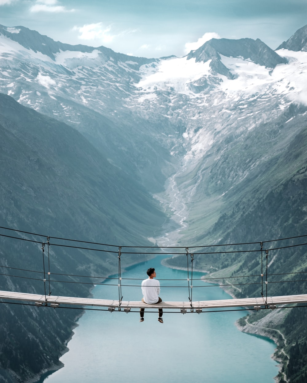 man wearing white shirt siting on bridge overlooking at mountain