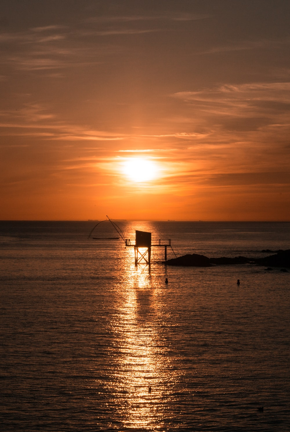 silhouette photography of a platform in the sea during golden hour