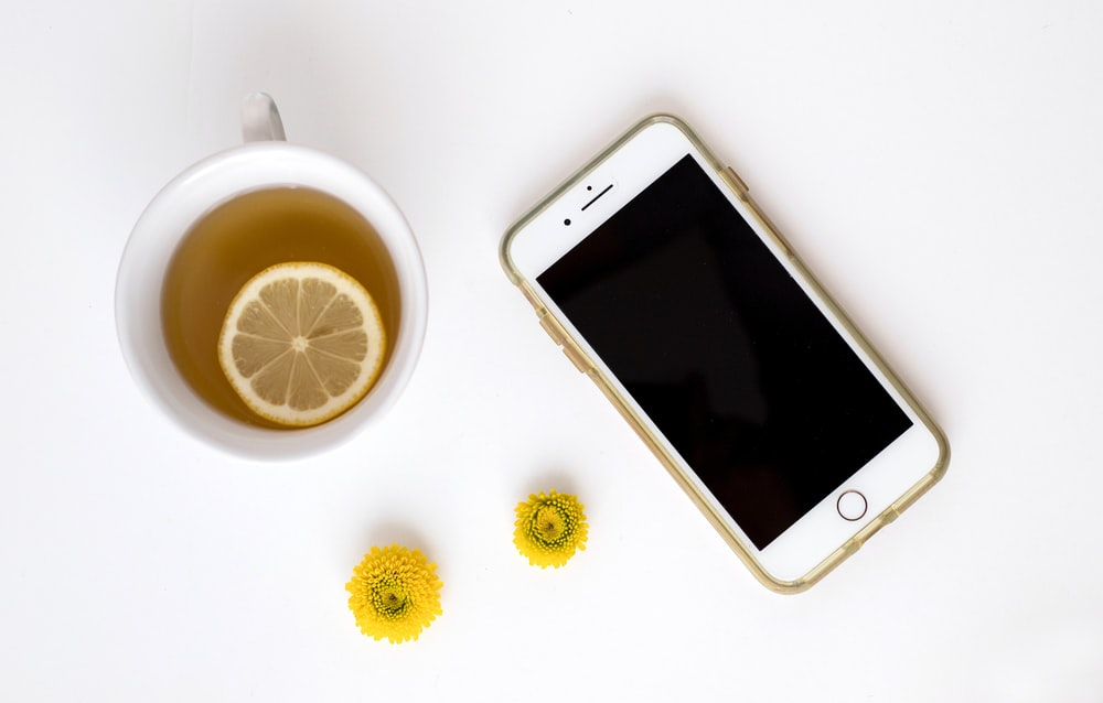 gold iPhone 8 plus near tea with sliced lemon