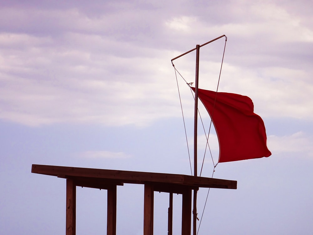 red flag hanging above a brown wooden shed