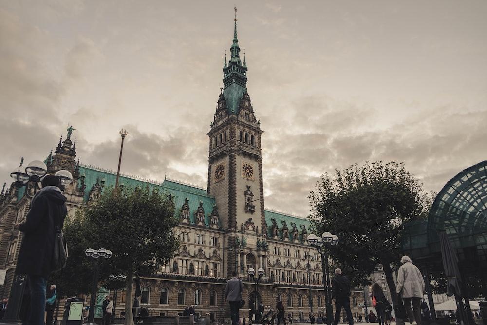 people walking near Hamburg City Hall in Germany under gray skies during daytime