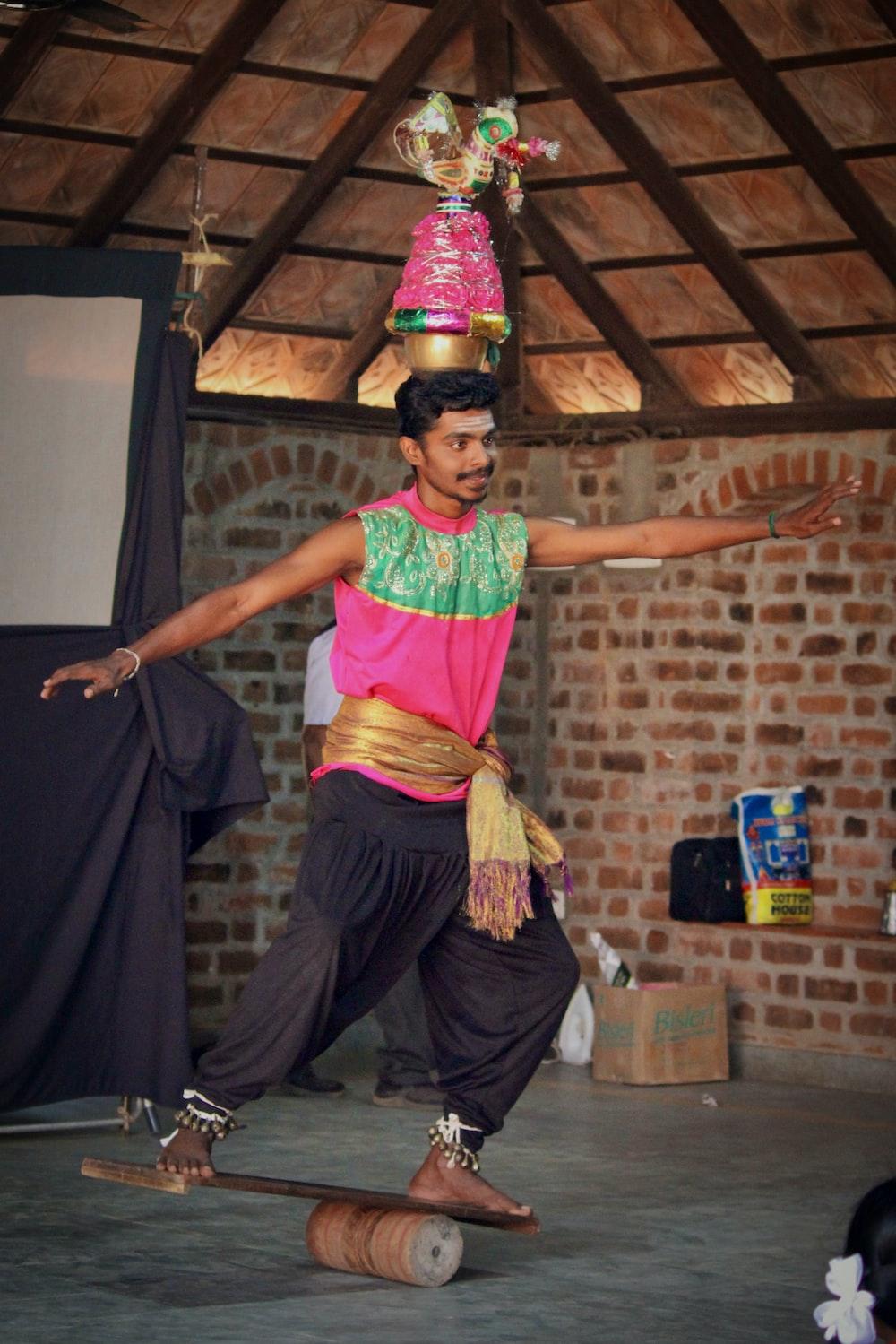 man balancing on board with jar on head