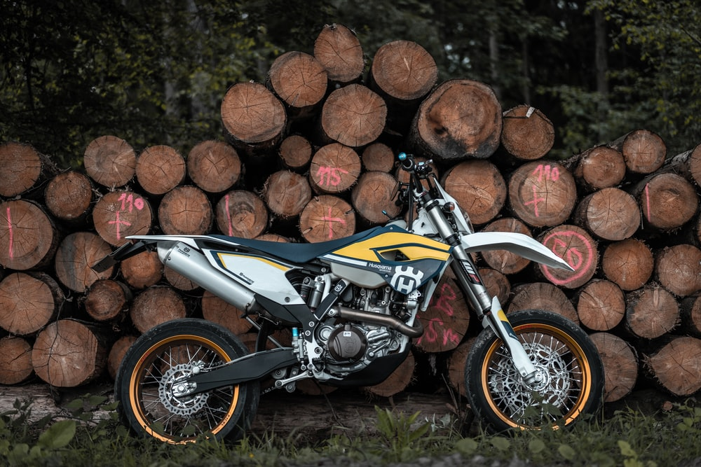 black, white, and yellow motocross dirt bike leaning on pile of tree log