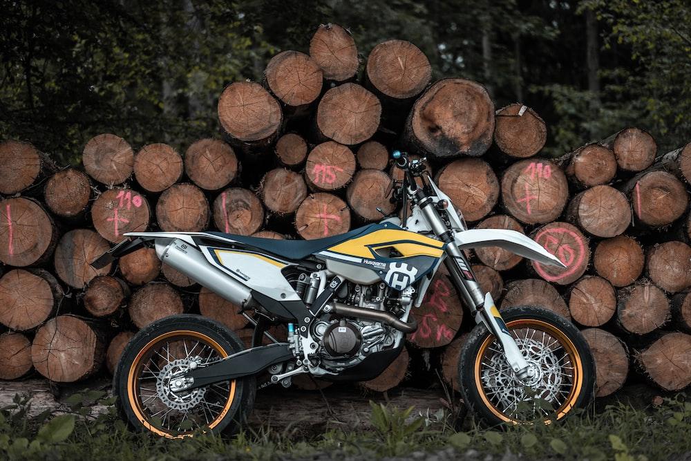 black, white, and yellow motocross dirt bike leaning on pile of tree log