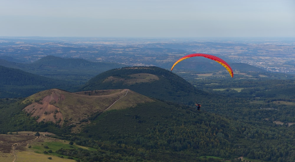aerial-photography of person paragliding near mountain