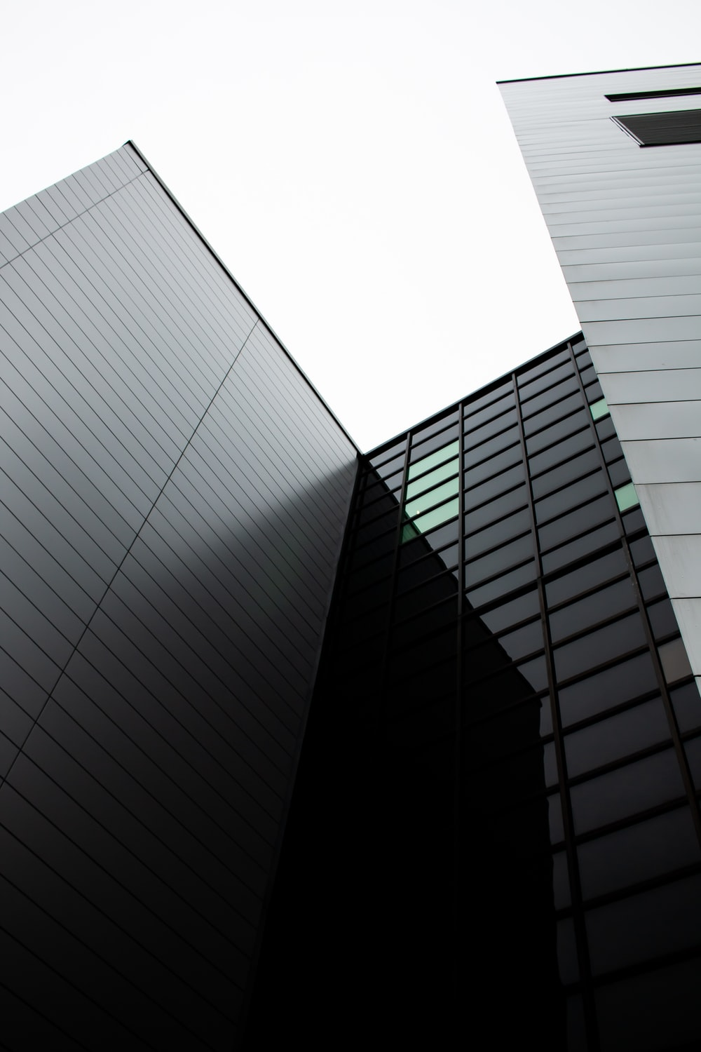 low-angle photography of clear glass walled buildings