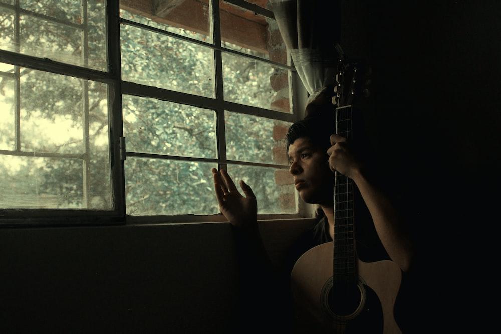 man holds guitar