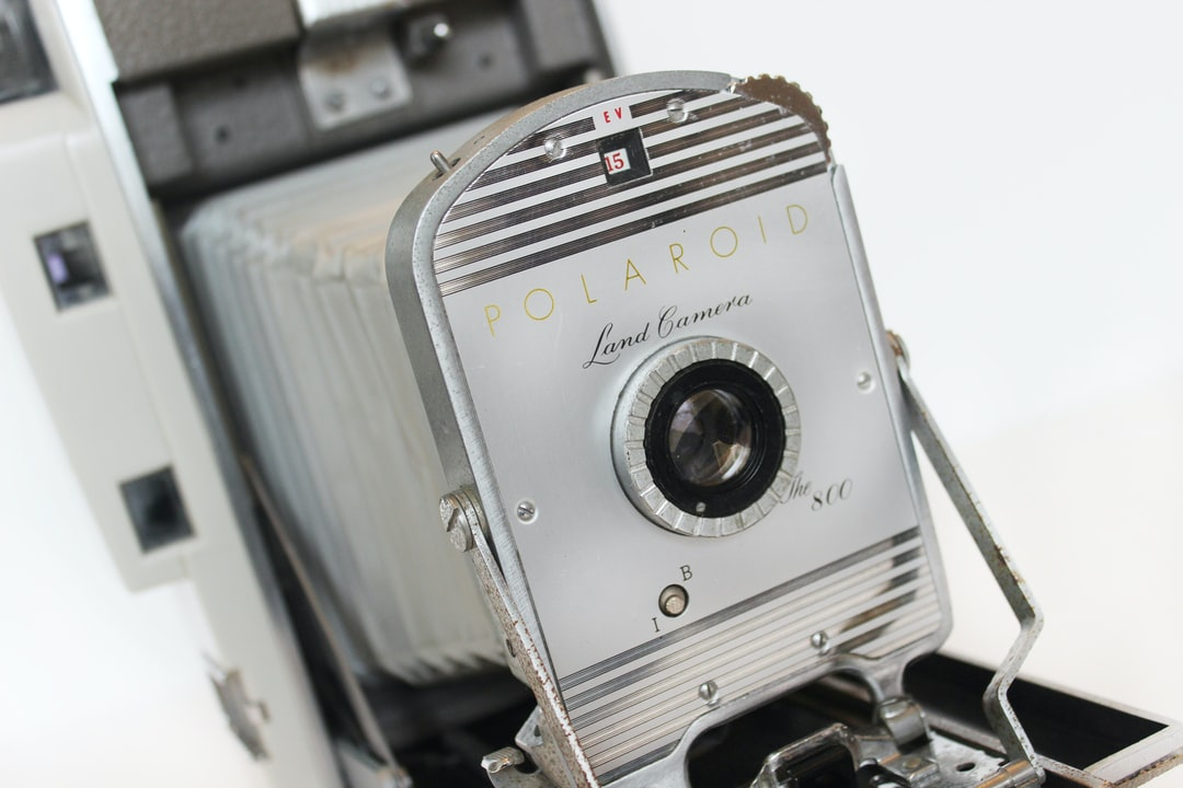 Vintage, retro Polaroid 800 Land Camera front lens and bellows details, gold lettering and chrome metal with clear glass lens on gray camera body.