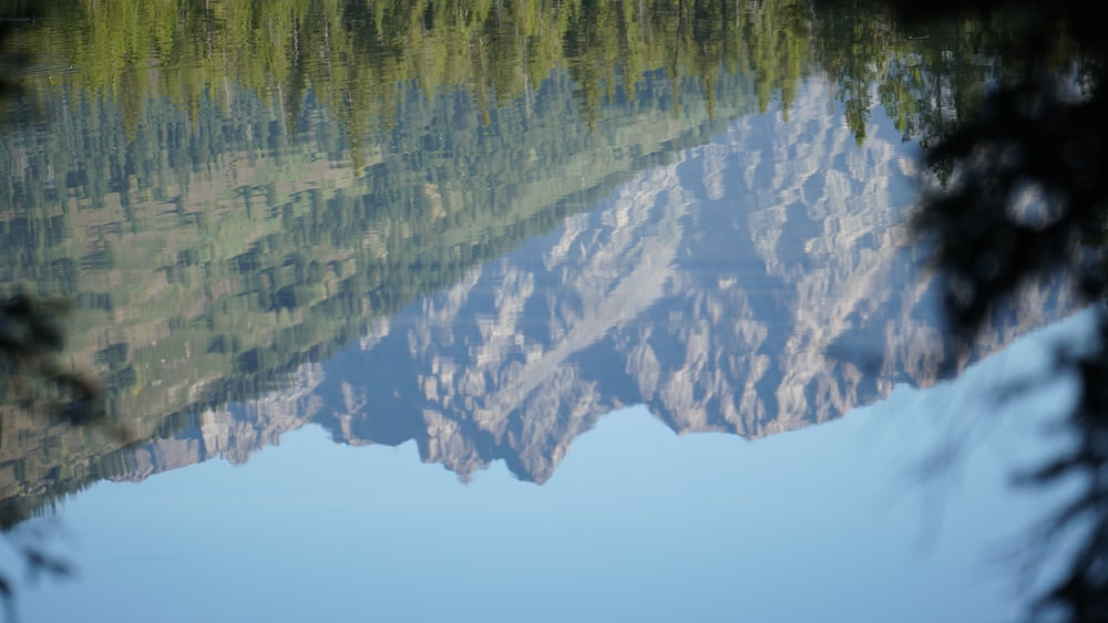 macro photography of body of water reflecting mountain during daytime