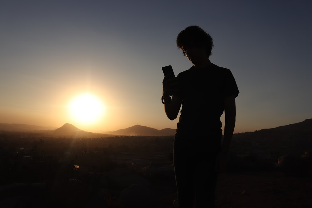 silhouette photo of man holding phone