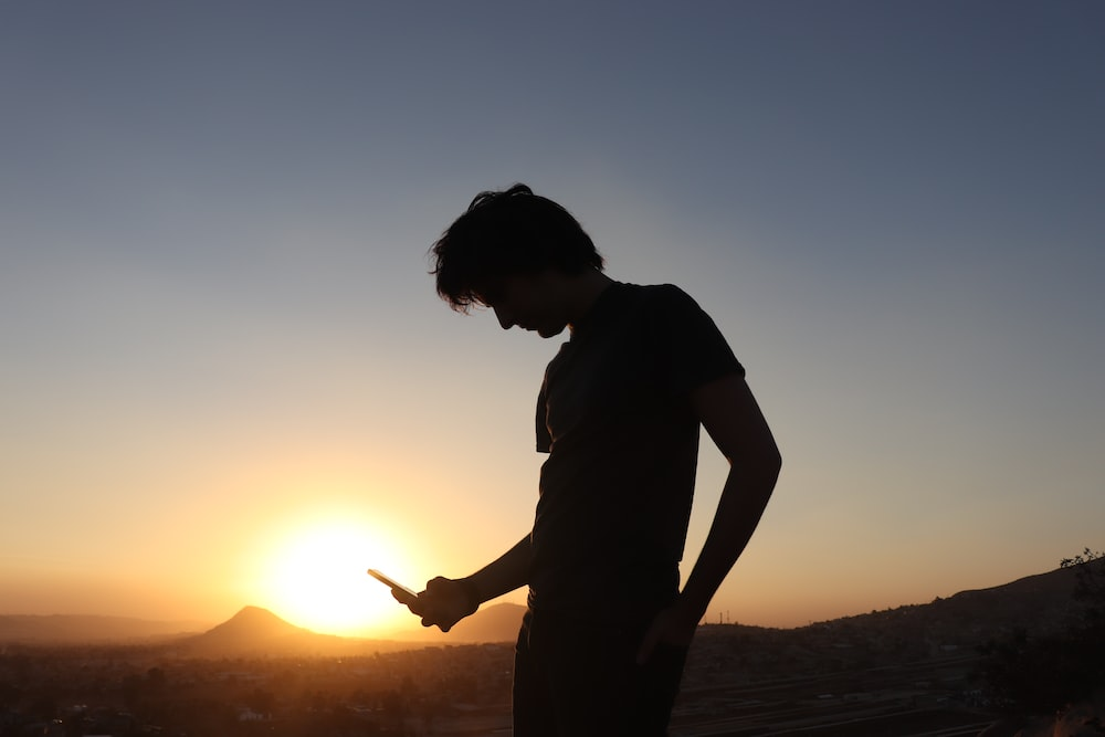 silhouette of person standing while looking down