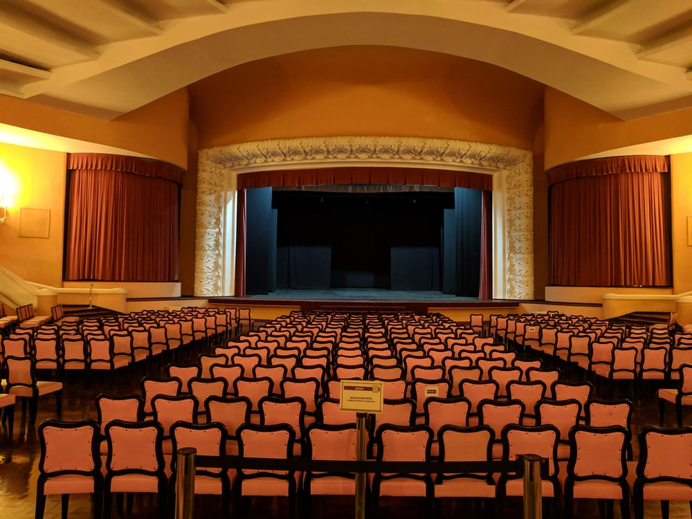 white-and-black chairs near stage inside building