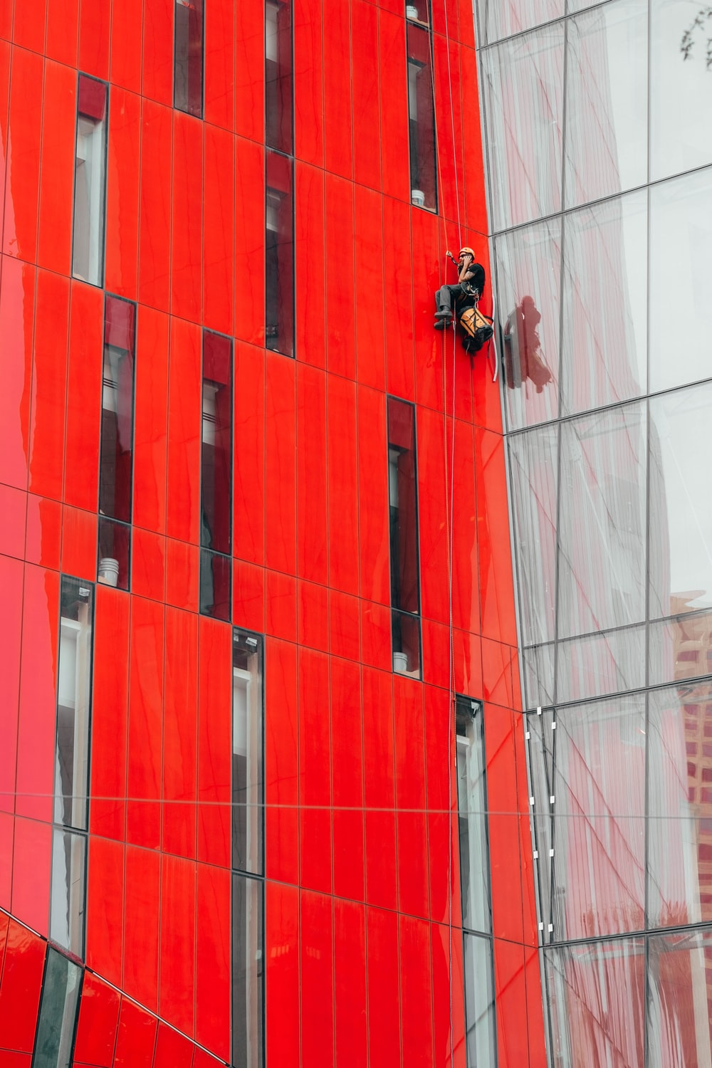 man climbing on red building