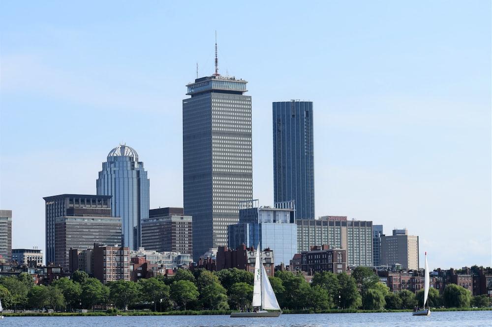 white sailing ship near high-rise buildings