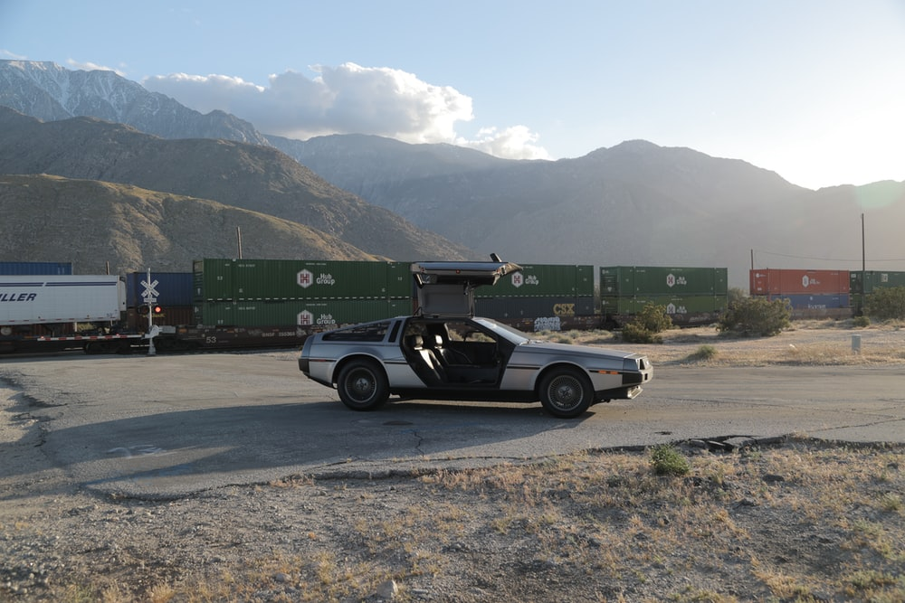 grey coupe near cargo trailers