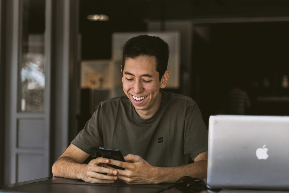 close-up photography of smiling man while holding phone beside silver MacBook