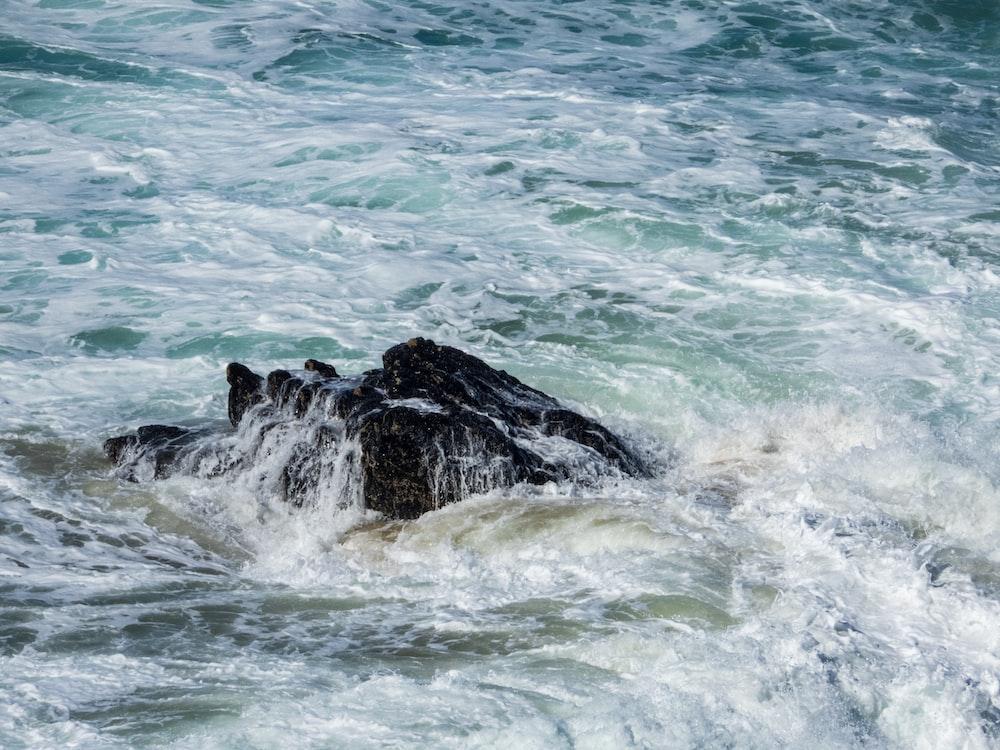 sea waves crashing on rock during daytime