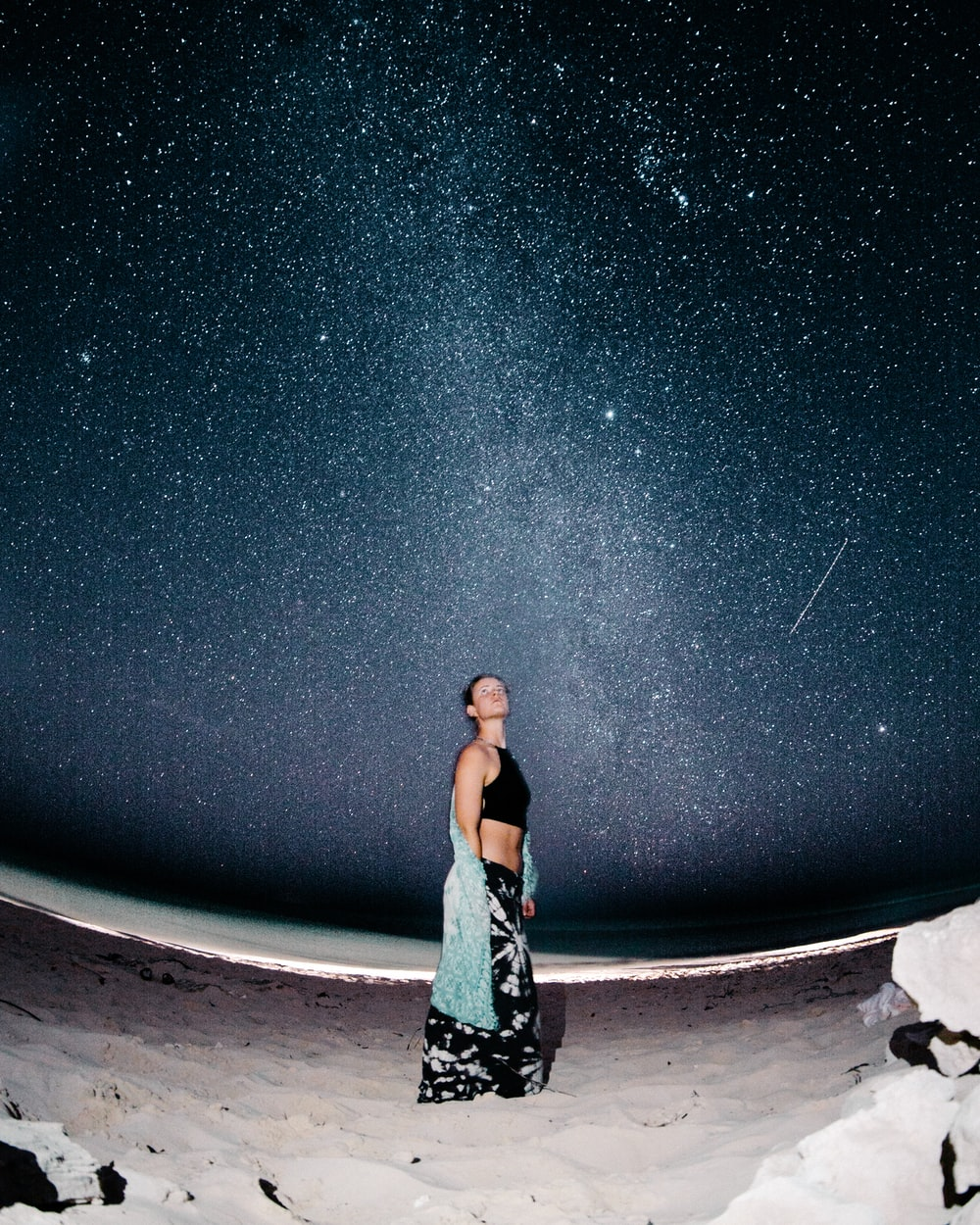 woman standing on sand at night