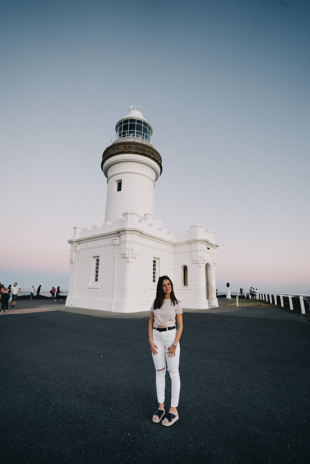 woman standing near white and black lighthouse