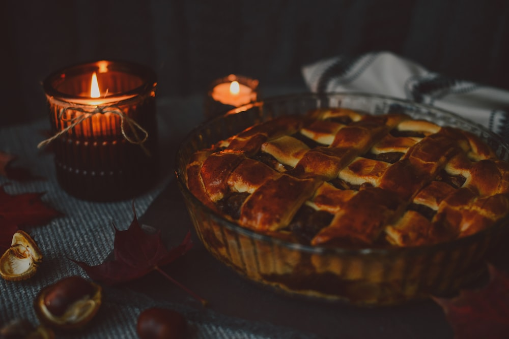 baked pie on glass bowl near tealight candles