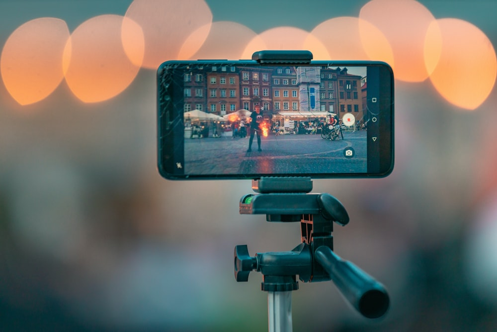 bokeh photography of a smartphone showing picture of the city street