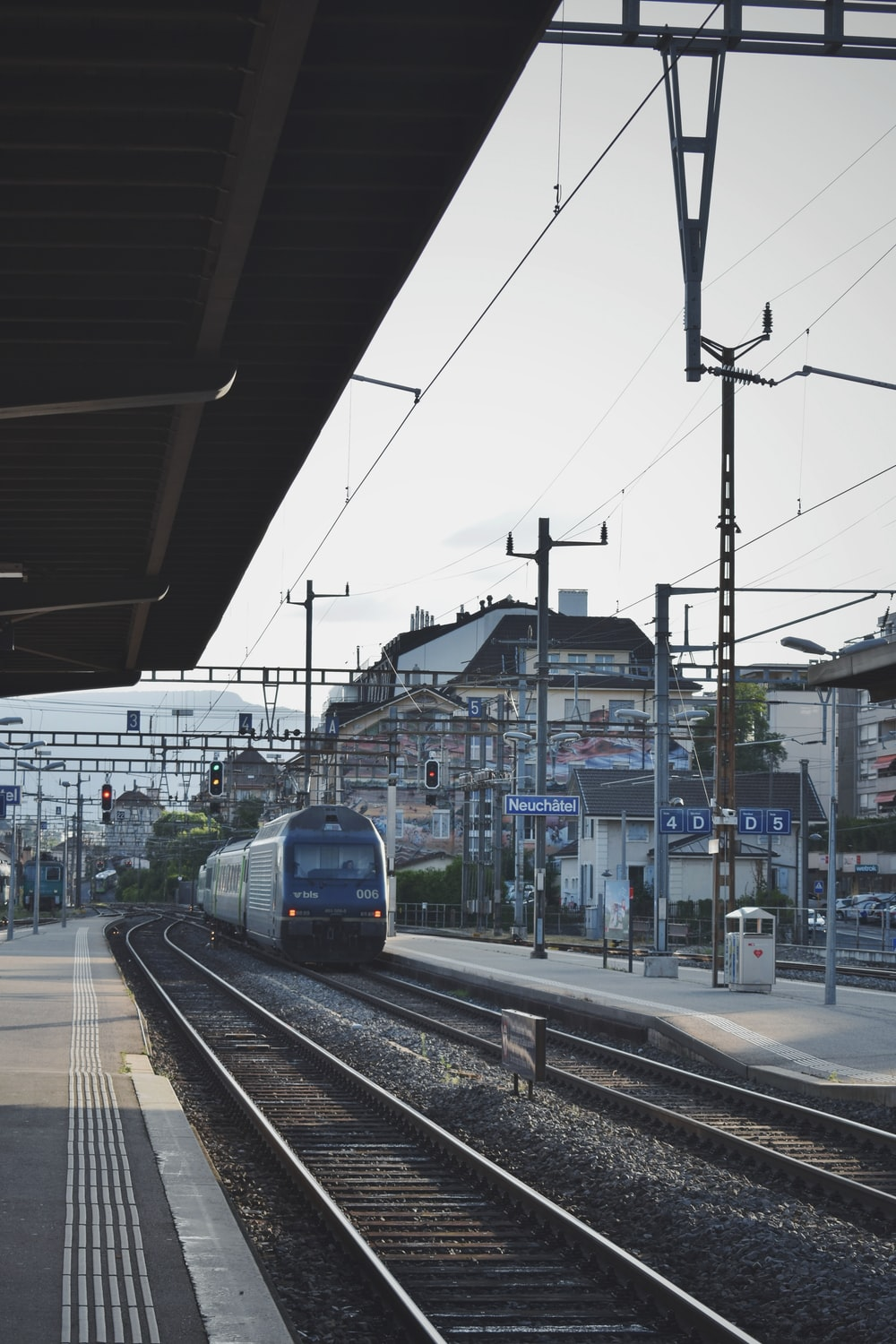 white and blue train near buildings during daytime
