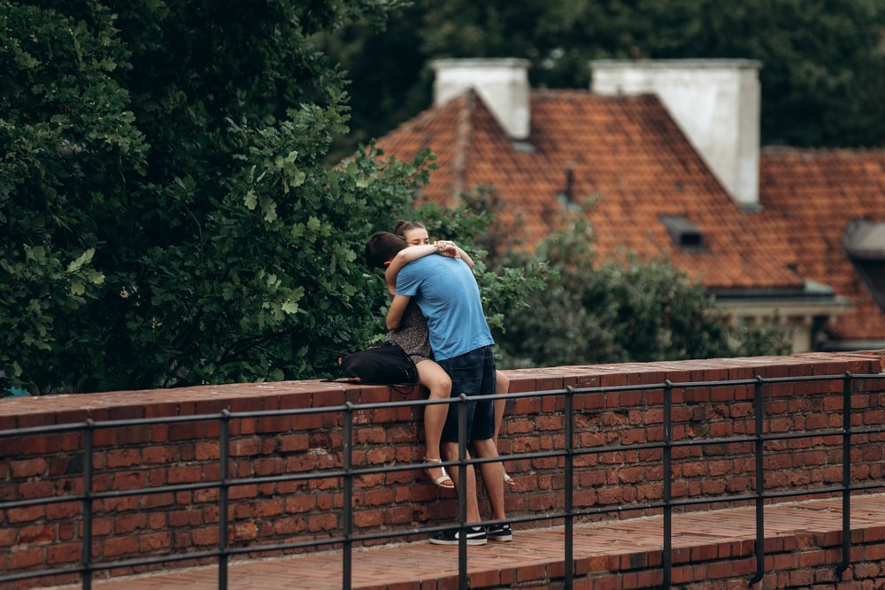 man and woman sitting on wall