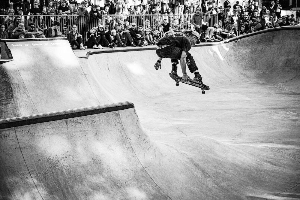 grayscale photo of man riding skateboard doing tricks