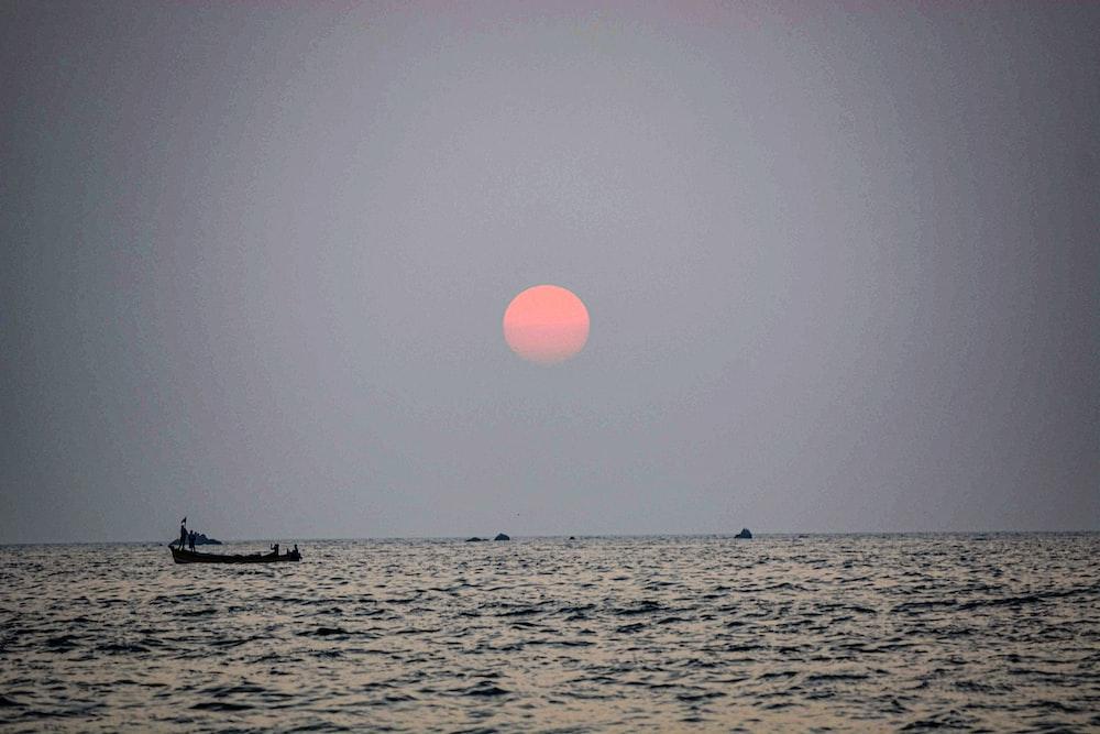 silhouette of boat on ocean