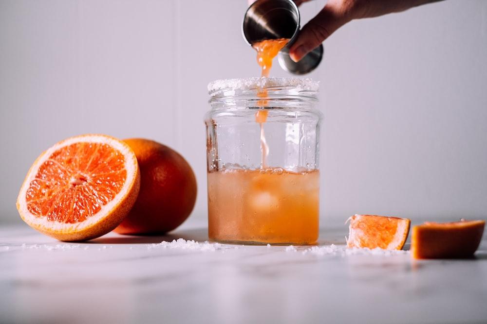 person pours liquid on jar near orange fruits