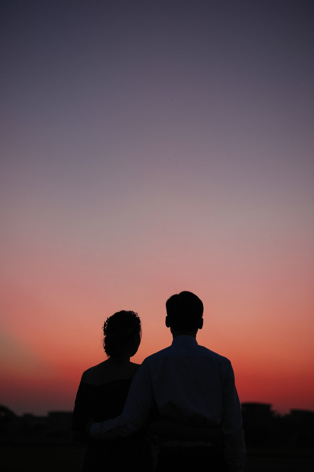 man and woman standing and looking sunset