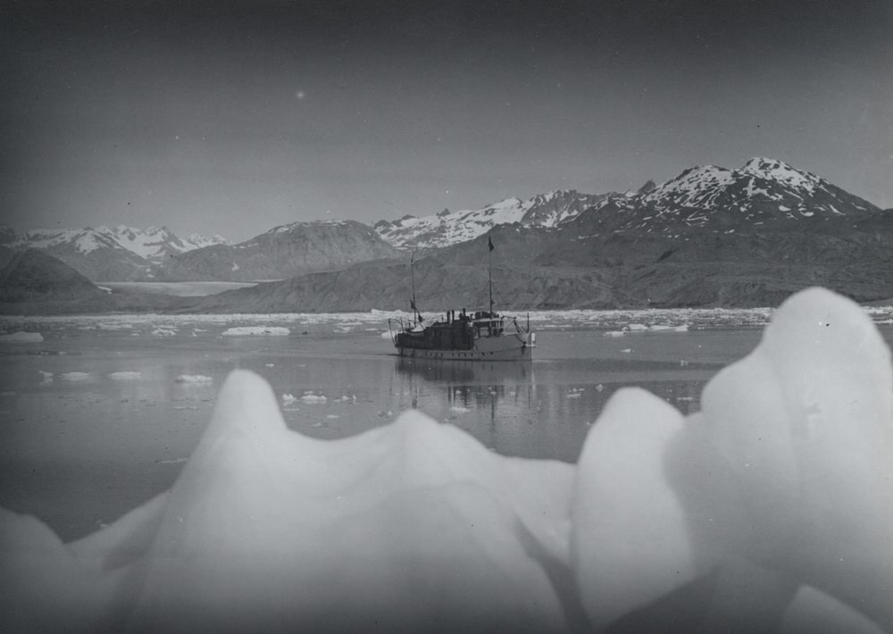 grayscale photo of boat near mountain