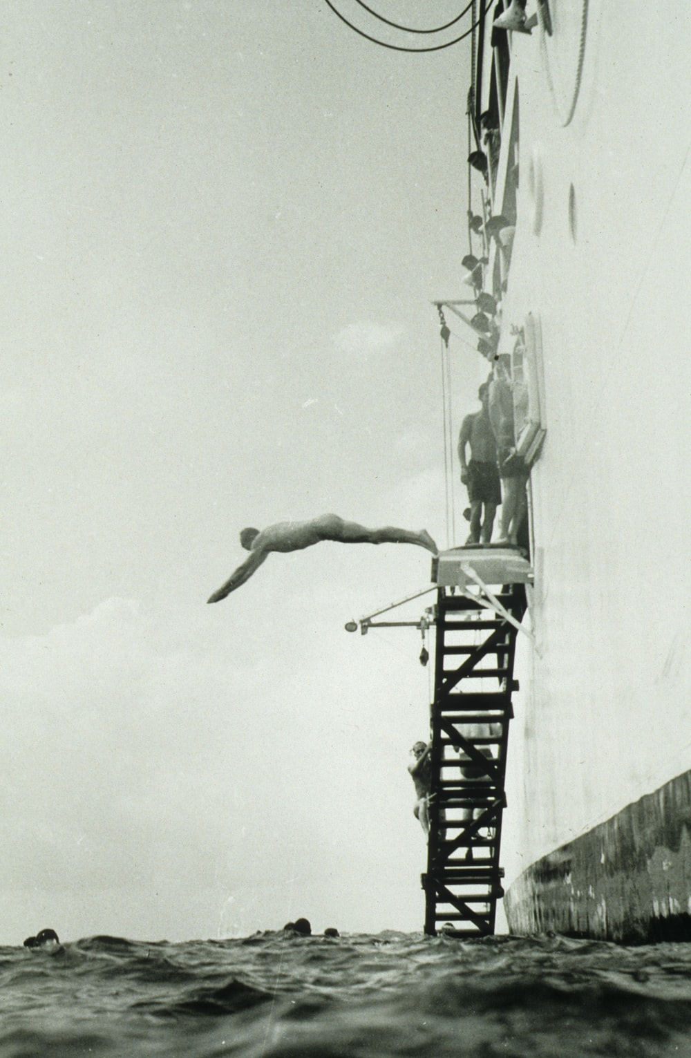 grayscale photography of man diving