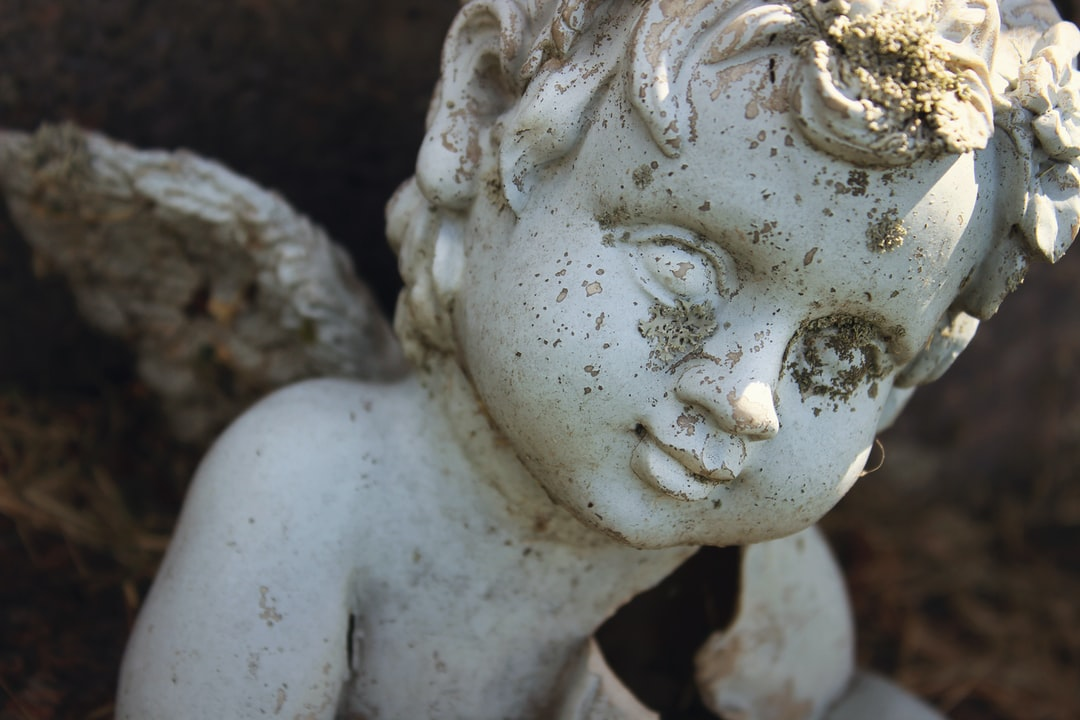 Concrete cherub angel with wings covered in moss and dirt in a cemetery or graveyard in early evening light.
