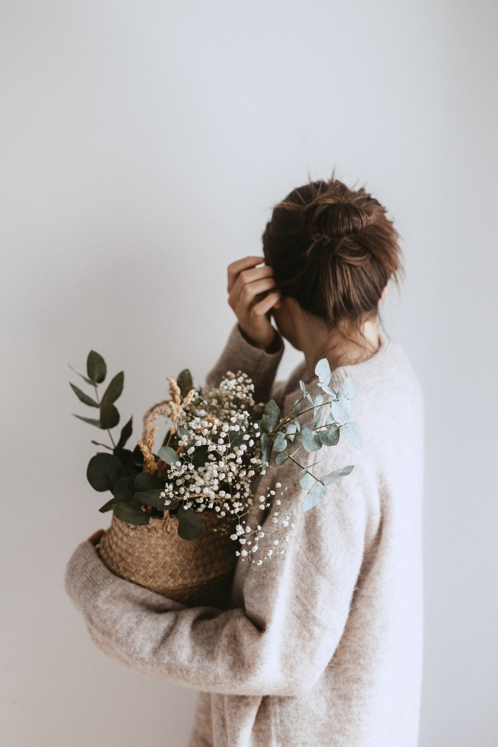 woman carrying white flower plant