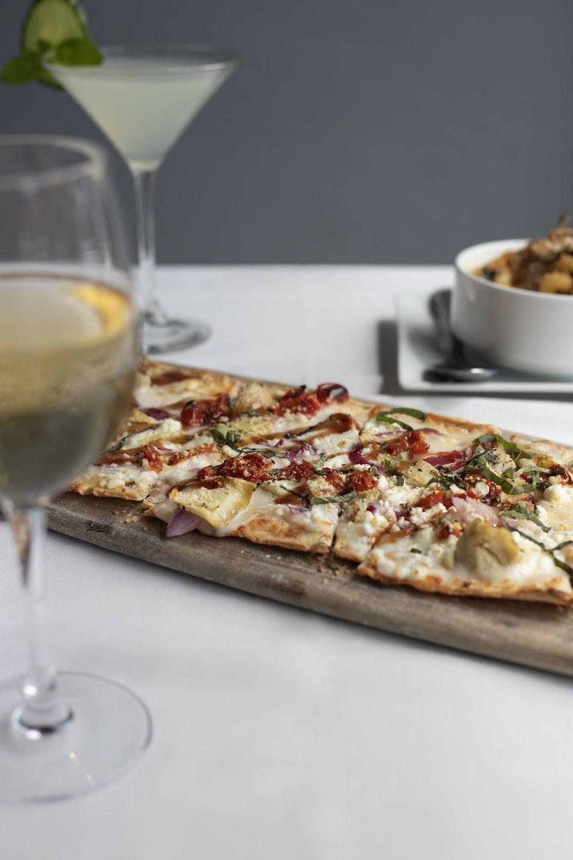 baked pizza near wine glass