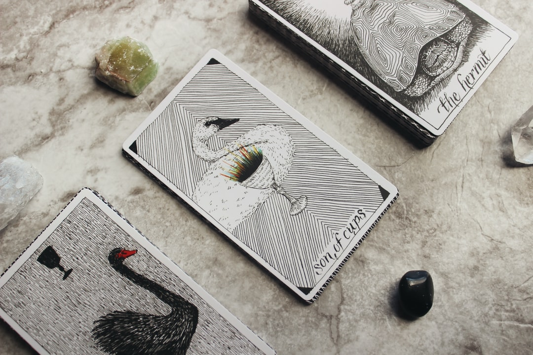 The Wild Unknown Tarot deck with three cards turned over for a tarot reading, surrounded by gemstones on a white marble table top.