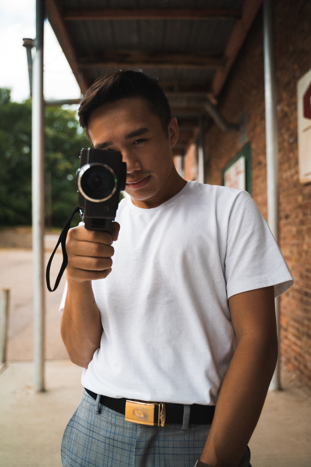 man wearing white crew-neck shirt holding video camera