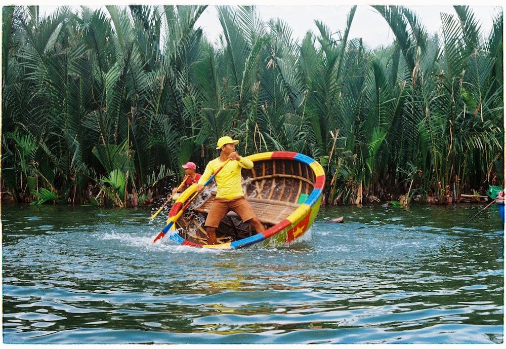 two men riding on boat near trees