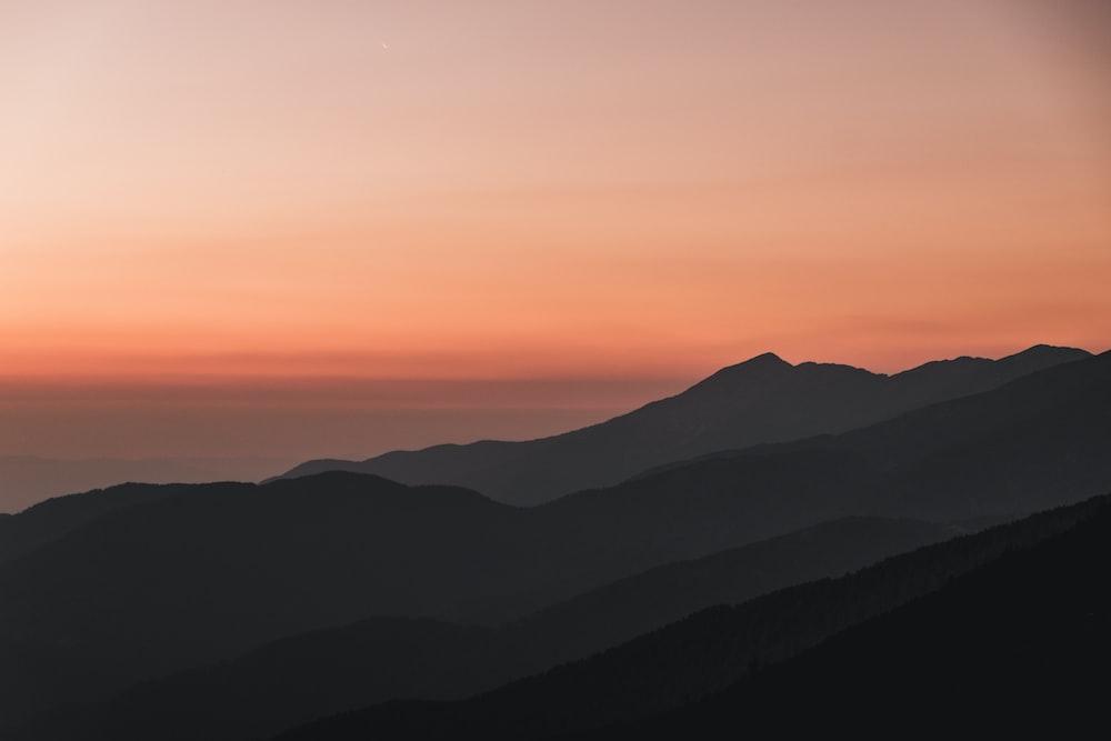silhouette mountain under orange sky