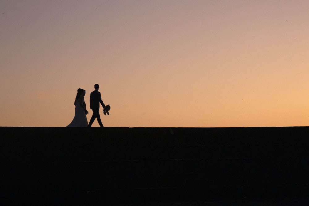 silhouette of two people during golden hour