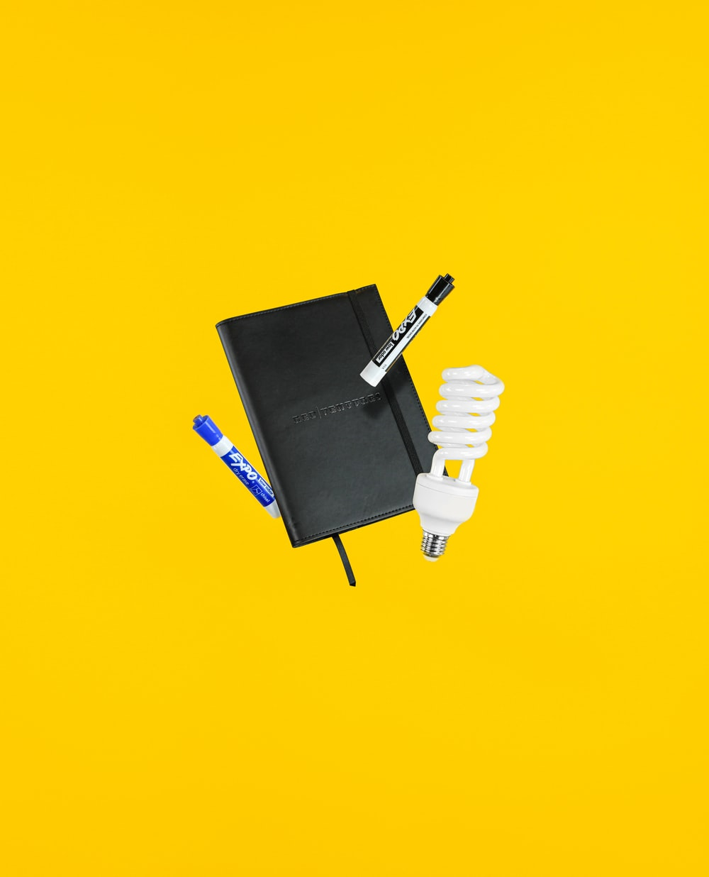 black and blue Expo markers near white CFL bulb and black hardbound book